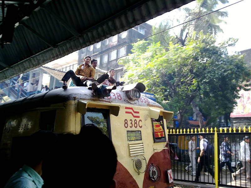 Passengers on the roof of a commuter EMU train in India